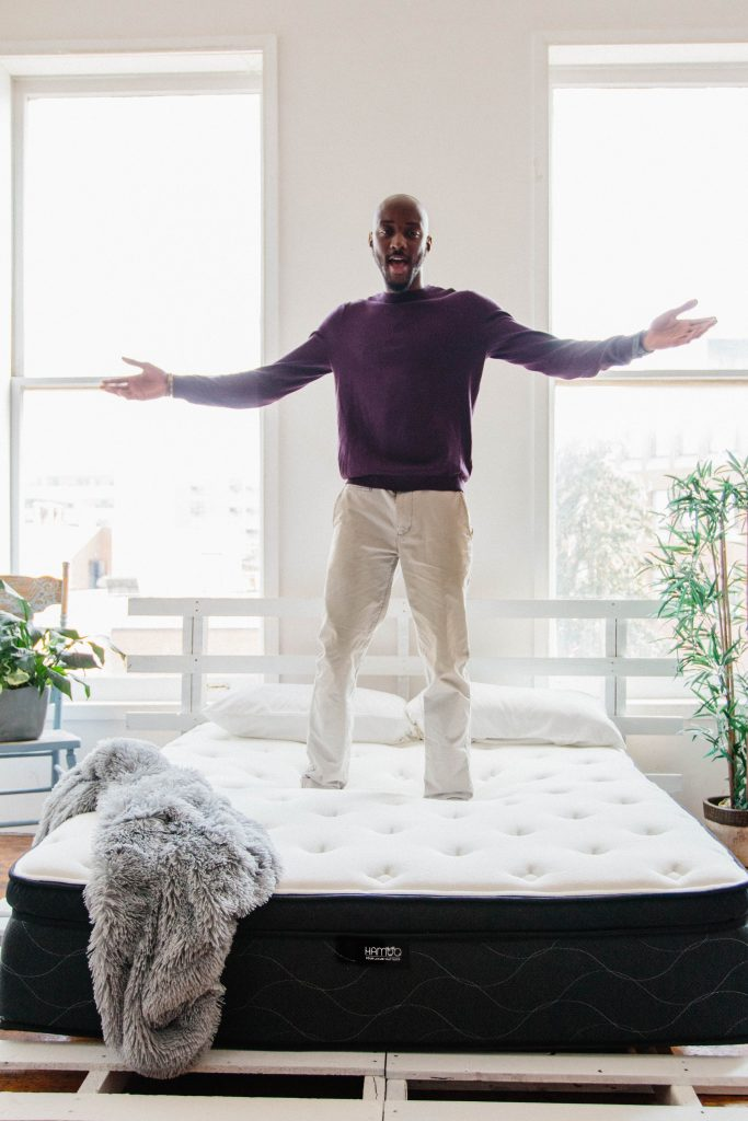 Man standing on mattress with arms wide open.
